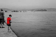Procesión marítima y niño pescando